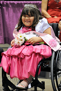 A smiling girl with a diadem, in a wheelchair (by courtesy of Miss Wheelchair California)