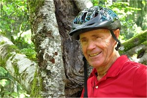 eldery with bike helmet in front of a tree (Rainer Sturm/pixelio.de)