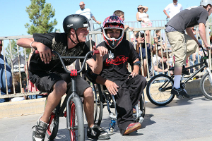 A boy leaning on a BMX bike apparently talks to a boy in a wheelchair.