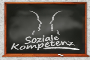 Two painted faces and the message: Social competences.