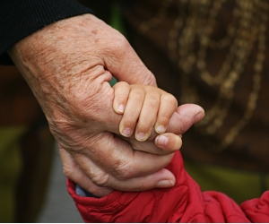 child's hand in old hand. (Bild: Angelina S./pixelio.de)